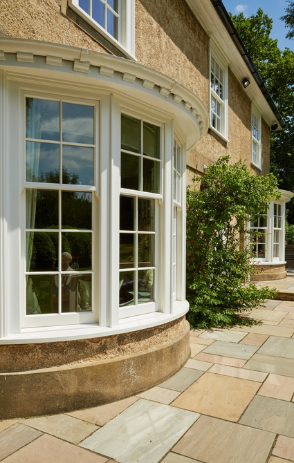 Faceted/shaped bay windows to the side elevation with a curved cill projection to finish
