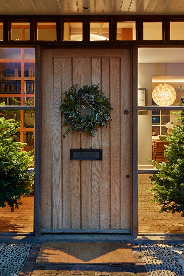 Boarded entrance door with letterbox and wreath