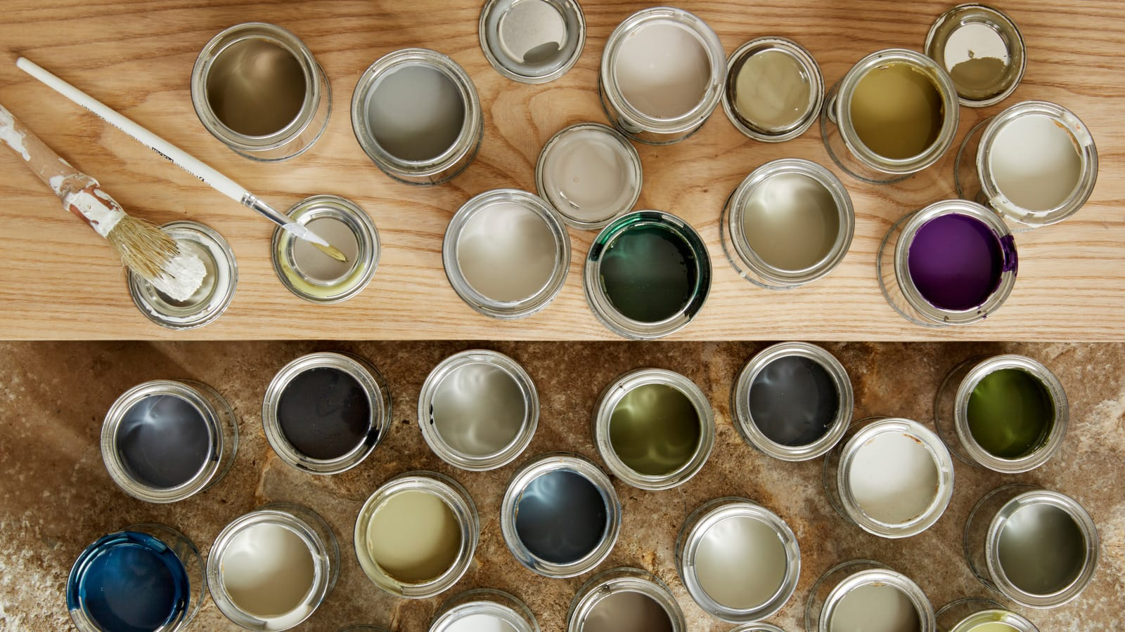 Coloured pots of paint on wooden surface