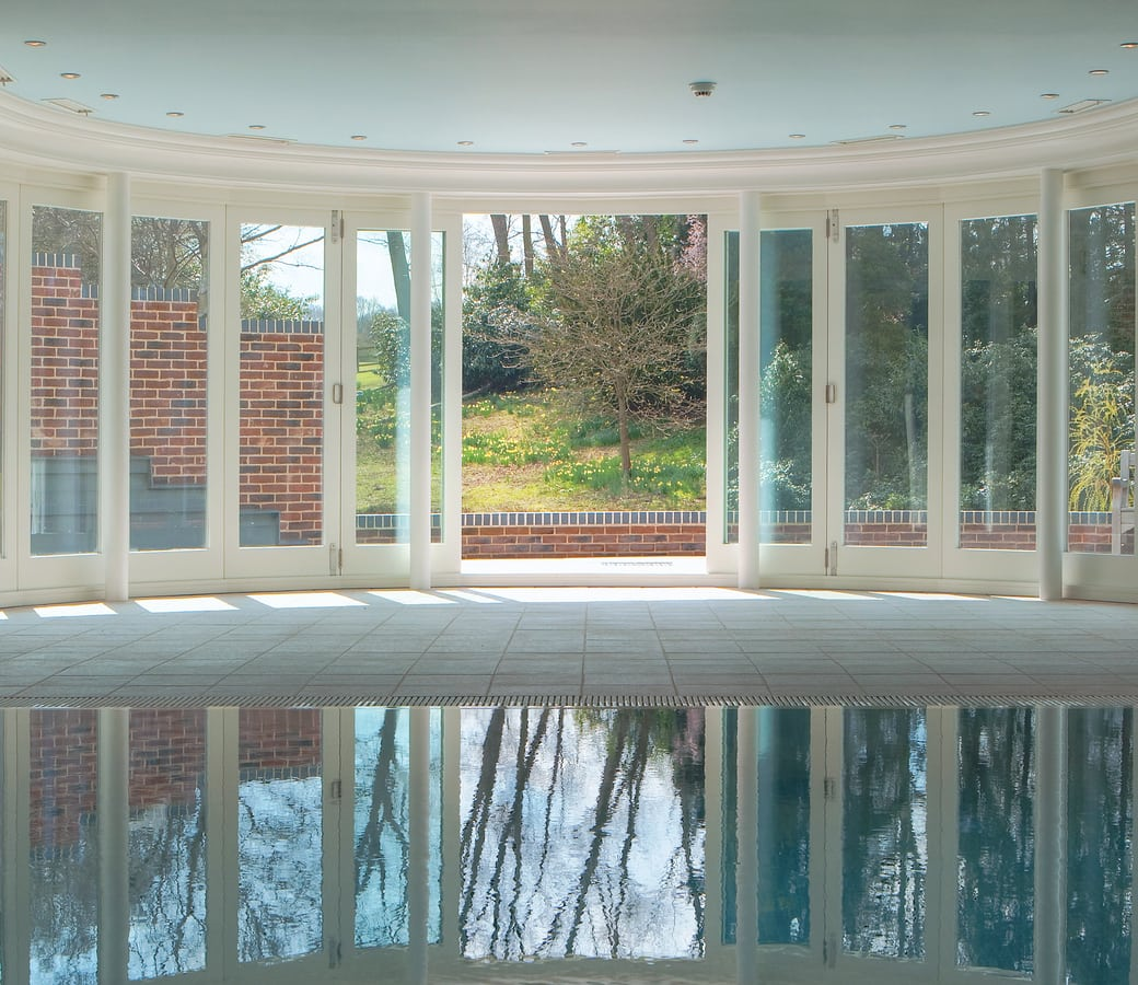 Ground floor swimming pool featuring a semi-circular timber folding door system