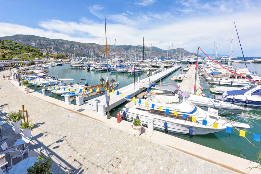 BEAULIEU-SUR-MER, FRANCE - JUNE 28, 2017: Daylight sunny view to parked yachts in port . People and childrens walking on sidewalk near boats. Mountains and bright blue sky with clouds on background.