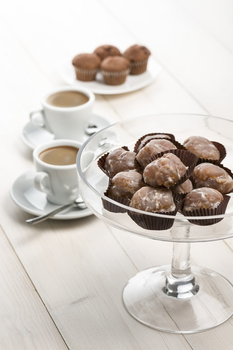 marron glace on glass tray on white table with cups of coffee