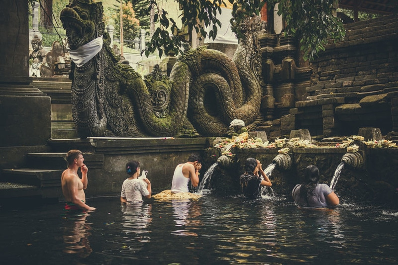 BALI, INDONESIA - DECEMBER 5, 2017: Holy spring water. People praying in the Tirta Empul temple. Bali.