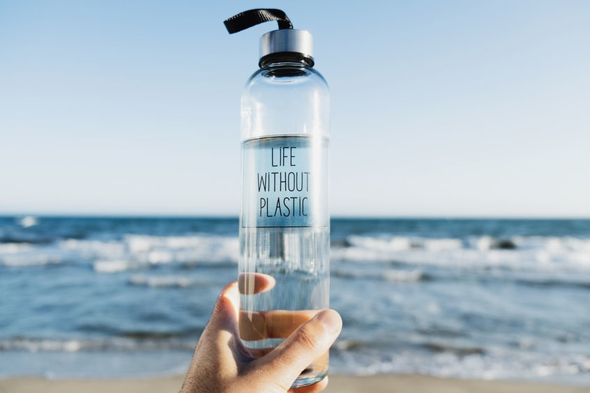 closeup of man holding a glass reusable water bottle with the text 'life without plastic' written in it, on the beach with the ocean in the background